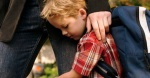 Son clinging to father's leg --- Image by © Klaus Tiedge/Corbis